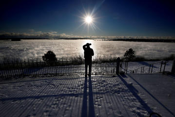 A man shields his eyes from the sun as he views the arctic sea smoke rising from Casco Bay, Thursday, Jan. 8, 2015, in Portland, Maine. Dangerously cold air has sent temperatures plummeting around the U.S.