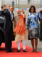 Indian Prime Minister Narendra Modi, center, U.S. President Barack Obama and first lady Michelle Obama wave to the gathering at the Palam Air Force Station in New Delhi, India, Jan. 25, 2015.
