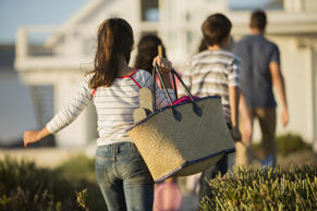 Girl with beach bag following her family to a beach house.