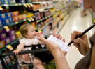 Woman with baby checking her list in grocery store.
