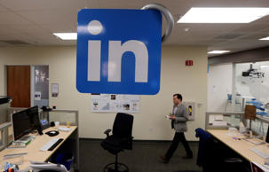 In this Nov. 6, 2014 photo, a LinkedIn employee walks past a company logo at the company's headquarters in Mountain View, Calif. LinkedIn reports quarterly financial results on Thursday, Feb. 5, 2015.