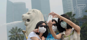Tourists in masks and sunglasses take a picture at Singapore's Merlion.