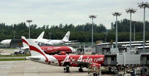 An AirAsia plane taxis while another is parked on the tarmac at the Changi International Airport in Singapore.