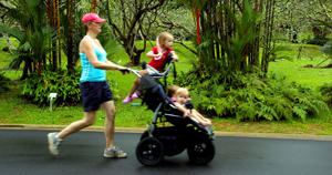 A woman jogs with her children in Singapore's Botanical Gardens.