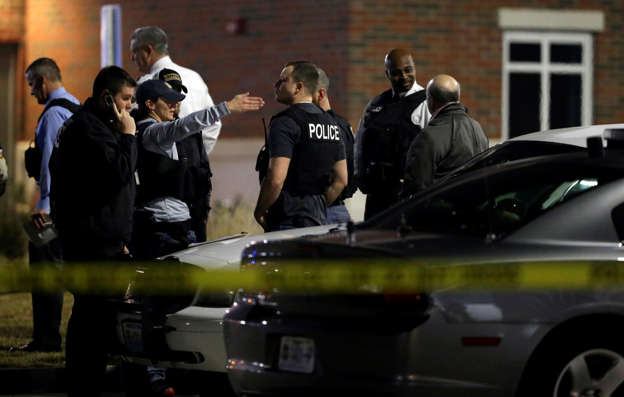 Police investigate the scene where two police officers were shot outside the Ferguson Police Department, March 12, 2015, in Ferguson, Mo.