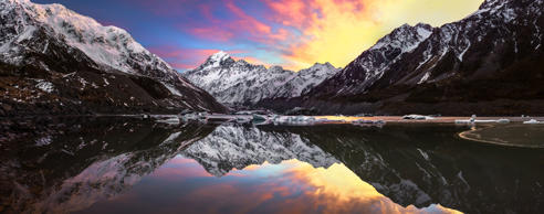 A colorful sunrise over the Hooker Valley in New Zealand. In the distance the peak of Mount Cook can be seen. The scene is reflected in the still water of the glacial lake.