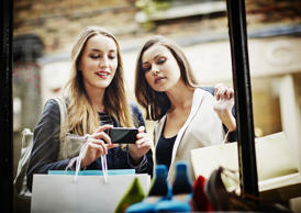 Young women window shopping, taking photograph with smartphone
