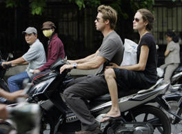 Brad Pitt (C) and his partner Angelina Jolie ride on a motorcycle on a busy street in downtown Ho Chi Minh city, 23 November 2006.