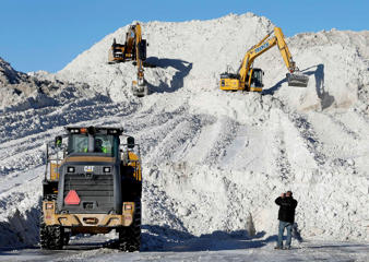 "Heavy equipment works on a mound of snow that has been cleared from city streets at a ""snow farm"" in Boston, Monday, Feb. 16, 2015. New England remained bitterly cold Monday after the region's fourth winter storm in a month blew through."