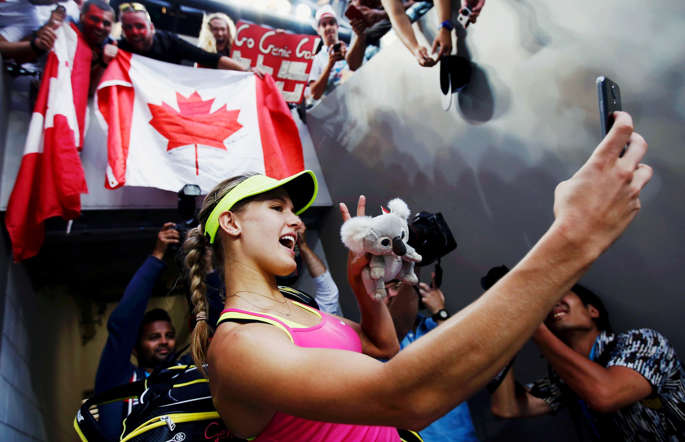 "Eugenie Bouchard of Canada takes a ""selfie"" using a spectator's phone after defeating Kiki Bertens of the Netherlands during their women's singles second round match at the Australian Open 2015 tennis tournament in Melbourne January 21, 2015."