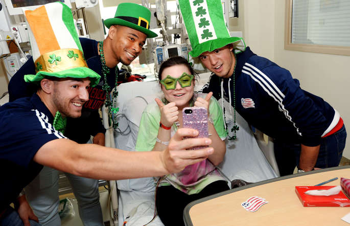 New England Revolution (L to R) Tyler Rudy, Charlie Davies, and Kelyn Rowe take a selfie with Belle at Boston Children's Hospital March 10, 2015 in Boston, Massachusetts.
