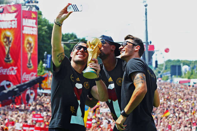 Germany's Lukas Podolski, Jerome Boateng and Mesut Oezil (L-R) pose for a 'selfie' with the World Cup trophy during celebrations to mark the team's 2014 Brazil World Cup victory, at a 'fan mile' public viewing zone in Berlin July 15, 2014.  Germany's victorious soccer team led by coach Joachim Loew returned home on Tuesday after winning the 2014 Brazil World Cup. A triumphant Germany team landed in Berlin on Tuesday to a hero's welcome, greeted by hundreds of thousands of jubilant Germans waving flags and wearing the national colours, revelling in the nation's fourth World Cup victory on Sunday in Brazil.