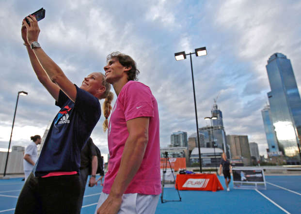 Denmark's Caroline Wozniacki (L)  takes a selfie with Spain's Rafael Nadal as they participate in a tennis promotional event in Melbourne January 16, 2015.