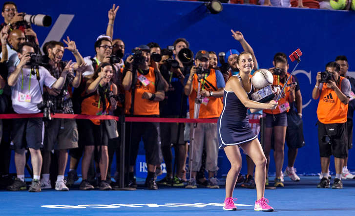 Timea Bacsinszky of Switzerland uses a selfie stick to take a photo of herself holding the trophy after she defeated Caroline Garcia of France to win the Mexico Open tennis tournament on Feb. 28, 2015, in Acapulco, Mexico.