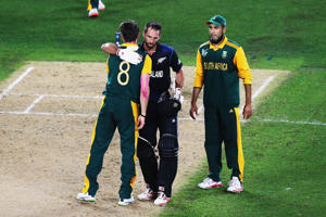 Imran Tahir of South Africa looks on as Grant Elliott of New Zealand hugs Dale Steyn of South Africa up after winning the 2015 Cricket World Cup Semi Final match between New Zealand and South Africa at Eden Park on March 24, 2015 in Auckland, New Zealand.