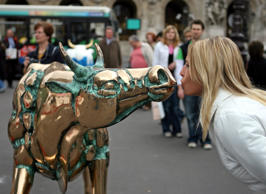 Tourist poses with cow sculpture displayed on Opera square in Paris.
