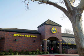 Pedestrians exit a Buffalo Wild Wings Inc., restaurant in San Ramon, California, U.S.