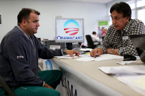 Ariel Fernandez, left, with an insurance  advisor as he signs up for the Affordable Care Act, also known as Obamacare, in Miami, Florida.