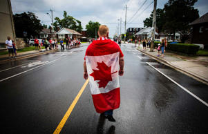Doug Ford walks with the Canadian flag draped on his back as he takes part in the East York Canada Day Parade in Toronto July 1, 2014.