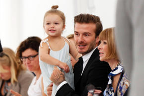 Former England soccer captain David Beckham holds his daughter Harper as he speaks to Vogue editor Anna Wintour while waiting for a presentation of the Victoria Beckham Spring/Summer 2014 collection during New York Fashion Week, September 8, 2013.