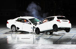 Toyota Motor Corp.'s Crown, left, and Vitz vehicles collide during a crash test at the company's Higashifuji Technical Center in Susono city, Shizuoka prefecture, Japan, on Thursday, July 21, 2011. Toyota demonstrated safety technologies aimed at the elimination of traffic accidents and fatalities to the media yesterday. Photographer: Haruyoshi Yamaguchi/Bloomberg