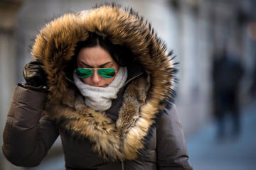 A woman shields herself as she walks through the cold and wind in New York's financial district February 13, 2015. Bitter cold temperatures were expected to grip much of the northeast U.S. Friday and through the weekend as some of the coldest air of the season moved into the region, according to local reports.
