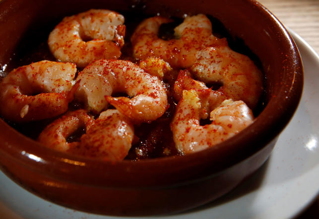 Gambas ajillo are prawns sautéed in garlic sauce and garnished with a gentle sprinkling of red chilli powder.