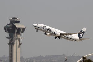 An Alaska Airlines jet passes the air traffic control tower at Los Angles International Airport during take-off on April 22, 2013 in Los Angeles, California.