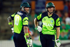 Ireland's John Mooney (L) wears a helmet with an extra guard attached as he stands with teammate Kevin O'Brien during the Cricket World Cup match against South Africa at Manuka Oval in Canberra March 3, 2015.