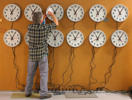 A worker cleans the faces of wall clocks being tested before they are shipped out at the Electric Time Company in Medfield, Massachusetts.