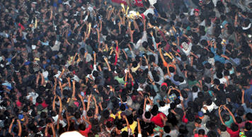 In this Thursday, March 5, 2015 photo, members of a mob raise their hands to take photos of a man, top center, accused of rape after he was lynched and hung in the city landmark Clock Tower in Dimapur, in the northeastern Indian state of Nagaland. Several thousand people overpowered security at Dimapur Central Prison in Nagaland on Thursday, and seized the rape suspect, whom they also accused of being an illegal migrant from Bangladesh. They pelted him with stones and beat him to death, said police Constable Sunep Aier.