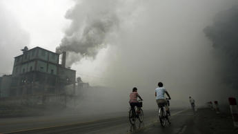Cyclists pass through thick pollution from a factory east of Beijing.
