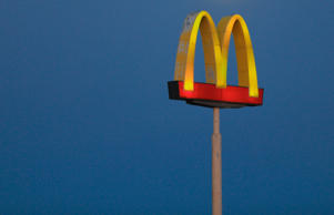 A full moon rises over the golden arches of a McDonalds store in Gretna, Neb., W...