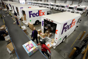 FedEx employees pull boxes from a conveyor belt and fill their trucks for deliveries at a FedEx sorting facility in the Bronx borough of New York on Dec. 15, 2014.