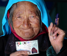 File: An Afghan resident holds her voter card after casting her ballot at a polling station in Bamiyan province on June 14, 2014.