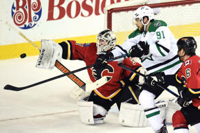 Calgary Flames goalie Karri Ramo (31) and Dallas Stars center Tyler Seguin (91) reach for the puck at Scotiabank Saddledome. Stars won 4-3 in a shootout.