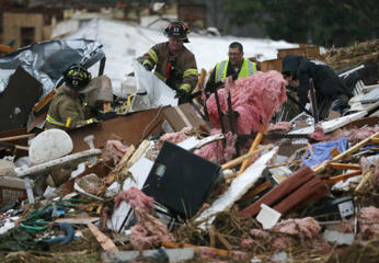 First responders work to free a man from a pile of rubble after a round of severe weather hit a trailer park near 145th West Avenue and West 17th Street in Sand Springs, Okla., March 25, 2015.