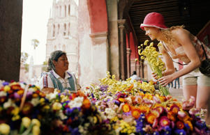 Tourist buying flowers from vendor in Mexican market.