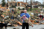 FILE - In this May 22, 2011 file photo, a man carries a young girl who was rescued after a tornado hit Joplin, Mo. In 2011 the United States saw one of the busiest tornado seasons in generations: Nearly 1,700 tornadoes that killed 553 people. With the planet heating up, many scientists seem fairly certain some weather elements like hurricanes and droughts will worsen. But as the traditional season nears, scientists are still trying to figure out if there be more or fewer tornadoes as global warming increases.