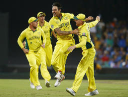 Australian bowler Mitchell Johnson (C) celebrates after wicket keeper Brad Haddin caught out India's Virat Kohli for one run during their Cricket World Cup semi-final match in Sydney, March 26, 2015.