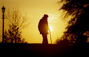 An elderly man strolls through a park.