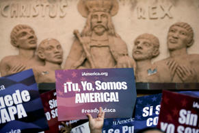 "A woman holds a sign that says in Spanish, ""you, me, we are America!"" during a rally in support of President Barack Obama's plan to protect more than 4 million people living illegally in the U.S. from deportation in front of a church Tuesday, Feb. 17, 2015, in San Diego."