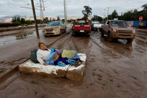 A woman rests on a mattress on a mud covered street after rains caused heavy flooding in Copiapo, Chile, Thursday, March 26, 2015. Unusually heavy thunder storms and torrential rains that began on Tuesday have blocked roads, caused power outages and affected some 600 people on this normally dry region. (