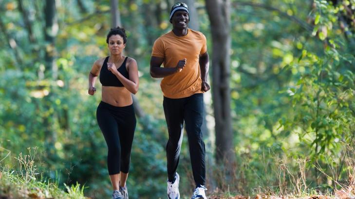 Couple jogging on gravel path.