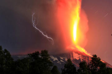 FILE - In this March 3, 2015 file photo, the Villarrica volcano erupts near Pucon, Chile. The eruption forced the temporary evacuation of residents and visitors. Many travelers to Pucon come to see the volcano and then realize there are many other things to see and do, including fishing and other types of recreation on Lake Villarrica.