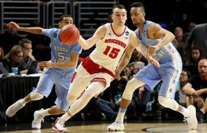 Sam Dekker #15 of the Wisconsin Badgers with the ball against Marcus Paige #5 and J.P. Tokoto #13 of the North Carolina Tar Heels in the second half during the West Regional Semifinal of the 2015 NCAA Men's Basketball Tournament at Staples Center on March 26, 2015 in Los Angeles.