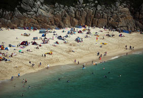 Holidaymakers enjoy the beachin Porthcurno, England.