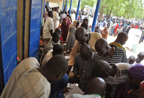 People in a camp for people that were displaced following attacks by Boko Haram, register to vote before casting their ballot later in the day, in Maiduguri, Nigeria, Saturday March 28, 2015. Nigerians went to the polls Saturday in presidential elections which analysts say will be the most tightly contested in the history of Africa's richest nation and its largest democracy.
