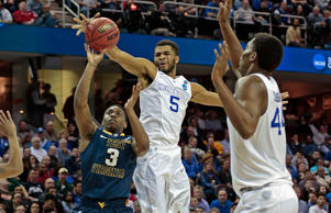 Kentucky's Andrew Harrison (5) blocks a shot by West Virginia's Juwan Staten (3) in the second half of the NCAA Tournament Sweet 16 game in the Midwest Region at Quicken Loans Arena in Cleveland on Thursday, March 26, 2015. Kentucky advanced, 78-39.