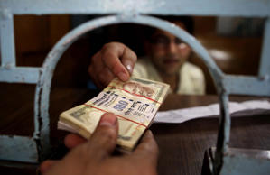 A clerk hands over cash to a customer at a bank in Srinagar, summer capital of Indian-controlled Kashmir, Aug. 29, 2013.